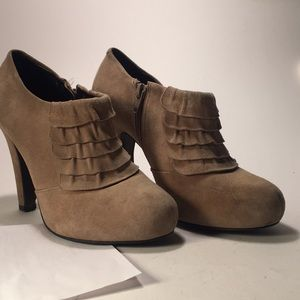 Brown zippered booties with ruffles across front